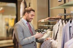 Homme dans le costume avec le smartphone au magasin d'habillement Photos stock