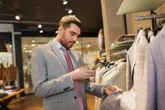 Homme dans le costume avec le smartphone au magasin d'habillement Photo stock