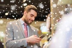 Homme dans le costume avec le smartphone au magasin d'habillement Photo libre de droits