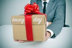 Homme dans le costume avec un cadeau avec le lendemain de Noël des textes Photographie stock