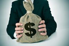 Homme dans le costume avec un sac d'argent de toile de jute Image stock