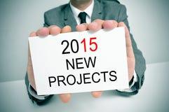 Homme dans le costume avec une enseigne avec les nouveaux projets des textes 2015 Image libre de droits