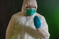 Homme dans le costume chimique inspectant les matériaux toxiques photos stock