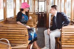 Homme dans le costume dans le wagon de train avec le regard de femme à l'un l'autre fac Photos stock