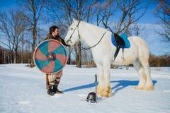 Homme dans le costume de la position antique de guerrier pr?s du grand cheval blanc image stock