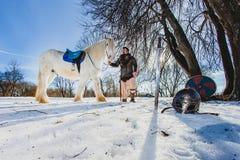 Homme dans le costume de la position antique de guerrier pr?s du grand cheval blanc photographie stock libre de droits