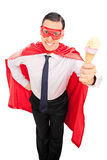 Homme dans le costume de super héros tenant une crème glacée  Images stock