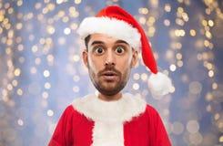 Homme dans le costume du père noël au-dessus des lumières de Noël Image libre de droits