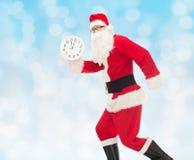 Homme dans le costume du père noël avec l'horloge Image stock