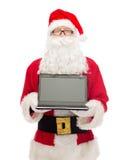 Homme dans le costume du père noël avec l'ordinateur portable Image stock