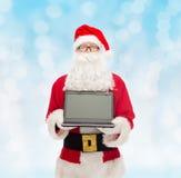 Homme dans le costume du père noël avec l'ordinateur portable Photos libres de droits