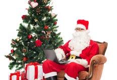 Homme dans le costume du père noël avec l'ordinateur portable Images libres de droits