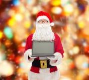 Homme dans le costume du père noël avec l'ordinateur portable Images stock