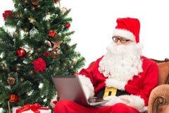 Homme dans le costume du père noël avec l'ordinateur portable Image libre de droits