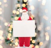 Homme dans le costume du père noël avec le panneau d'affichage Photo stock