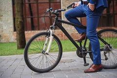 Homme dans le costume faisant un cycle sur la rue photos stock