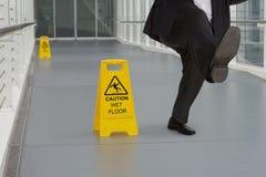 Homme dans le costume glissant sur le plancher humide Photo stock