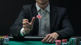 Homme dans le costume jetant des puces en l'air pour prendre la décision au sujet des paris, lent-MOIS de jeu banque de vidéos