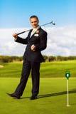 Homme dans le costume jouant le golf Photographie stock libre de droits