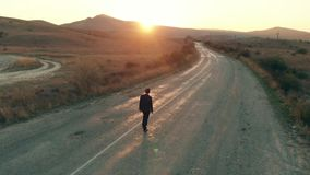 Homme dans le costume marchant loin par la route banque de vidéos