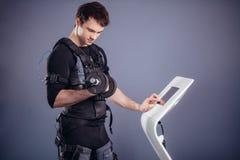 Homme dans le costume musculaire électrique de stimulation se tenant avec des haltères Photos libres de droits