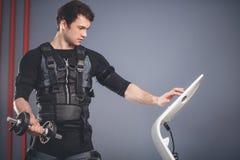 Homme dans le costume musculaire électrique de stimulation se tenant avec des haltères Images stock