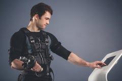 Homme dans le costume musculaire électrique de stimulation se tenant avec des haltères Images libres de droits