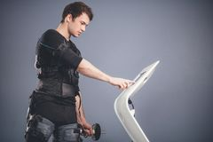 Homme dans le costume musculaire électrique de stimulation se tenant avec des haltères Image libre de droits