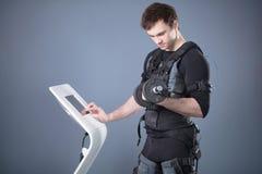 Homme dans le costume musculaire électrique de stimulation se tenant avec des haltères Photo libre de droits