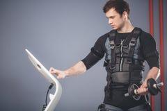 Homme dans le costume musculaire électrique de stimulation se tenant avec des haltères Image stock