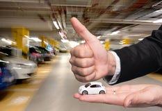 Homme dans le costume noir tenant le petit modèle de voiture et montrant le signe correct Image libre de droits
