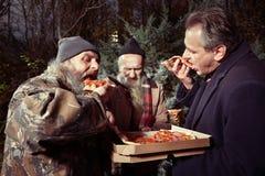 Homme dans le costume partageant la pizza avec deux hommes sans abri affamés Photos stock