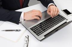 Homme dans le costume se reposant avec l'ordinateur portable Photographie stock libre de droits