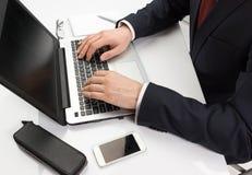 Homme dans le costume se reposant avec l'ordinateur portable Image stock