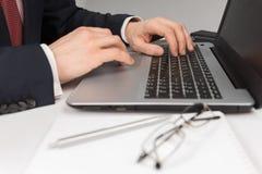 Homme dans le costume se reposant avec l'ordinateur portable Image libre de droits