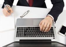 Homme dans le costume se reposant avec l'ordinateur portable Photos stock