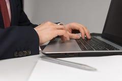Homme dans le costume se reposant avec l'ordinateur portable Photos libres de droits