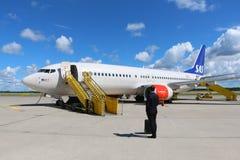 Homme dans le costume se tenant près d'une avion de ligne Photographie stock libre de droits