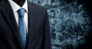 Homme dans le costume sur un fond de mur en béton Photographie stock libre de droits