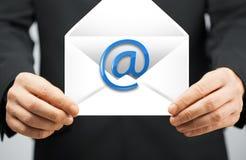 Homme dans le costume tenant l'enveloppe avec le signe d'email Photo stock