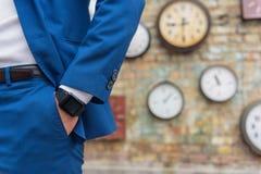 Homme dans le costume tenant le mur proche avec des horloges image stock