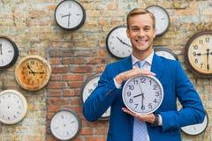 Homme dans le costume tenant le mur proche avec des horloges photo libre de droits
