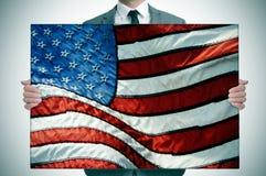 Homme dans le costume tenant un drapeau américain images libres de droits