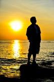 Homme dans le coucher du soleil Image stock