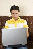 Homme dans le divan avec l'ordinateur portatif Photo stock