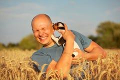 Homme dans le domaine de blé, lumière d'après-midi, tenant le terrie de Jack Russell image libre de droits