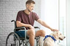 Homme dans le fauteuil roulant avec le chien de service Photo stock