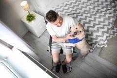 Homme dans le fauteuil roulant avec le chien de service Photographie stock libre de droits