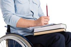 Homme dans le fauteuil roulant avec des livres photo libre de droits