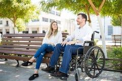 Homme dans le fauteuil roulant avec son amie Images libres de droits